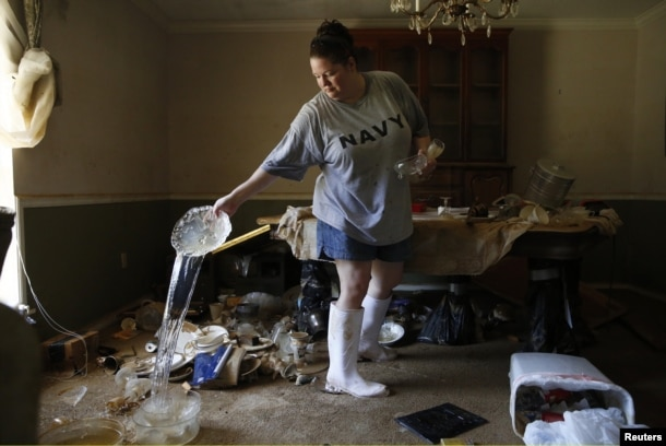 Marilyn Mays drains water from dishes in the dining room of her mother's home after heavy rains led to flooding in Denham Springs, Louisiana, Aug. 17, 2016.