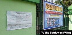Tempelan kertas berisi jadwal Penerimaan Peserta Didik Baru (PPDB) untuk sekolah dasar negeri ditempel di pintu masuk salah satu SD Negeri di Solo, Minggu, 14 Juni 2020. (Foto: Yudha Satriawan/ VOA)