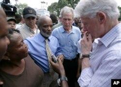 El expresidente de Haití, Rene Preval, segundo a la izquierda, el expresidente George W. Bush, al centro, y el expresidente y enviado especial de la ONU para Haití, Bill Clinton, right, durante una visita a un campo de sobrevivientes en Puerto Príncipe luego del terremoto de 2010. (03/22/10)