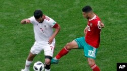 L'Iranien Masoud Shojaei et le Marocain Younes Belhanda lors du match du groupe B entre le Maroc et l'Iran à la Coupe du monde de football 2018 à Saint-Pétersbourg, Russie, le 15 juillet 2018.