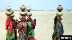 Village women walk through the desert in search for water in Pakistan.