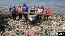 Nelayan Indonesia mendorong perahunya di antara sampah plastik yang memenuhi pantai Sukaraja di Bandar Lampung, 8 September 2019. (Photo by PERDIANSYAH / AFP)