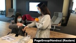 An employee has her temperature checked before entering PageGroup's office after reopening, as the coronavirus disease (COVID-19) continues, in Shanghai, China, April 29, 2020.