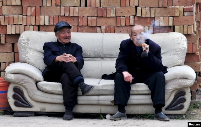 FILE - An elderly man (R) smokes a pipe as he chats with another man on a sofa in front of piles of bricks in Yongji, Shanxi province, China. In China, the government's policy is to have 90 percent of old age care in the home, seven percent at the community level and just three percent in retirement homes.