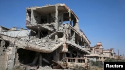 FILE - Buildings damaged during clashes between troops loyal to Libya's eastern government and the Shura Council of Libyan Revolutionaries are seen during a cleanup of the debris in Benghazi, Libya April 24, 2016.