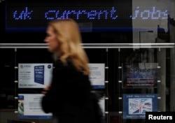 FILE - A pedestrian walks past an employment center in London.