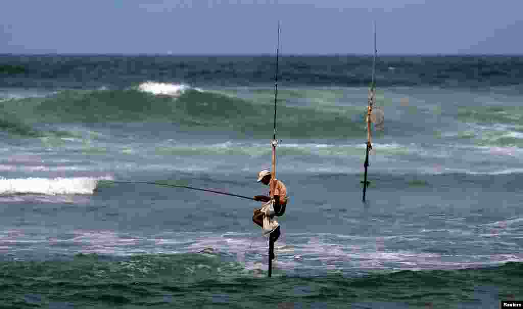 A fisherman catches fish as he sits atop a stilt in the sea in Koggala, Sri Lanka.