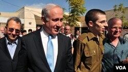 Prajurit Israel yang dibebaskan Hamas, Gilad Shalit (kedua dari kanan), bersama ayahnya, Noam Shalit (kanan) dan PM Israel Benjamin Netanyahu (18/10).