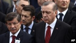 FILE - Turkey's President Recep Tayyip Erdogan (R) and Prime Minister Ahmet Davutoglu (L) arrive to attend funeral prayers for army officer Seckin Cil, who was killed in Sur, Diyarbakir, in Ankara, Turkey, Feb. 18, 2016.