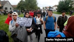 Hundreds of migrants stuck in Serbia set off on foot toward the border with Hungary to protest its closure for most people trying to reach the European Union.