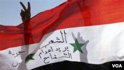 Para warga asing di Suriah menyuarakan solidaritas mereka di kota Mafrag, dekat perbatasan Jordania-Suriah (19/8). Tulisan di bendera tersebut berbunyi 'masyarakat ingin pembunuh dieksekusi'.
