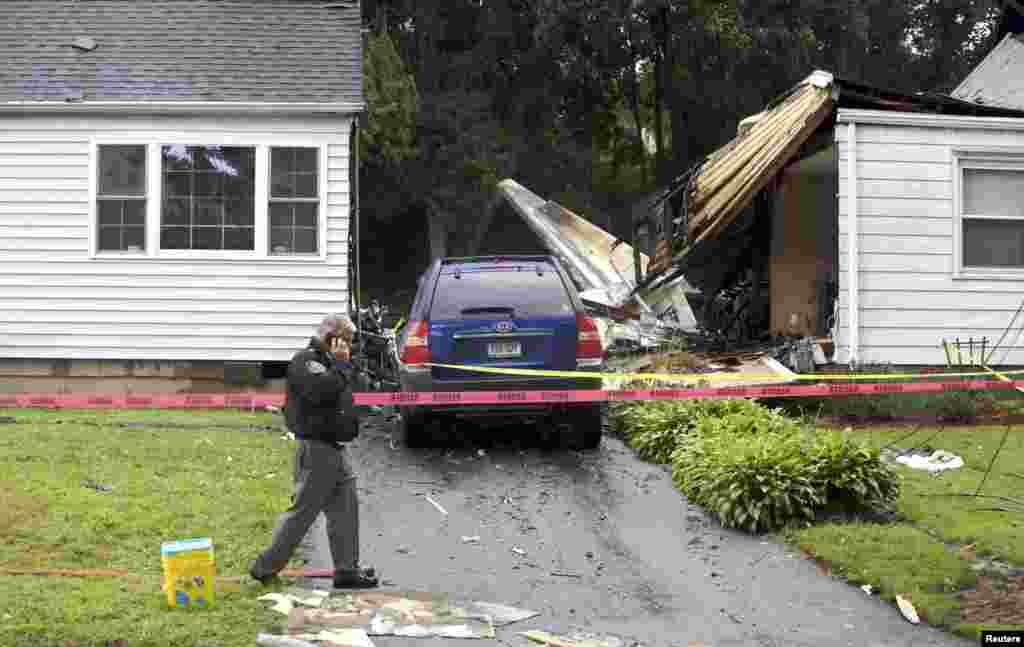 The remains of a plane is seen next to a damaged home after it crashed in East Haven, Connecticut, USA, Aug. 9, 2013. Two bodies have been located after a small plane crashed into two houses and the death toll could rise, Governor Dannel Malloy said.