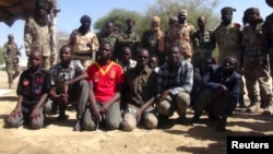 Former members of insurgent group Boko Haram gather in front of Chadian soldiers in Ngouboua, Chad, April 22, 2015. The young men said they were Chadian nationals forced to join Boko Haram while studying the Quran in Nigeria, and that they escaped and tur