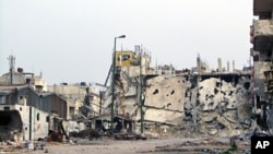 A handout picture made available by the General Committee of the Syrian Revolution shows destroyed buildings in Inshaat district of Homs, March 7, 2012
