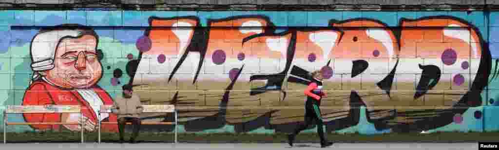 A jogger runs past graffiti on a sunny Spring day in Vienna, Austria.