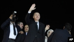 Turkish Prime Minister Recep Tayyip Erdogan , center, and his wife Emine wave to the crowd upon their arrival at the Ataturk Airport of Istanbul early June 7, 2013.