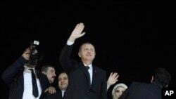 ນາຍົກລັດຖະມົນຕີເທີກີ ທ່ານ Recep Tayyip Erdogan (ກາງ) ແລະພັນລະຍາຂອງທ່ານ ຍານາງ Emine ໂບກມື ໃຫ້ແກ່ຝູງຊົນ ຂະນະທີ່ເດີນທາງໄປຮອດ ສະໜາມບິນອິສຕັນ ບູລ ໃນຕອນເຊົ້າຂອງວັນສຸກມື້ນີ້.