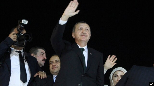 Turkish Prime Minister Recep Tayyip Erdogan (C) and his wife Emine wave to the crowd upon their arrival at the Ataturk Airport of Istanbul early June 7, 2013.