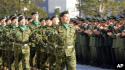 Japan Ground Self Defense Forces Col. Kimihito Iwamura, center, leads about 100 soldiers of a Japanese army contingent during a send-off ceremony at the Defense Agency in Tokyo Friday, Jan. 7, 2005. Japan's pro-U.S. government extended a one-year humanita