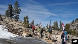 Mary Small, right, looks up at the bony and barren terrain typically skied in Sequoia National Park as she and other backcountry skiers hike back to civilization from the Pear Lake cabin, April 1, 2015.