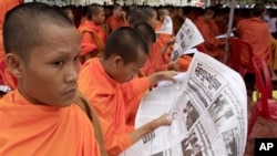 Cambodian monks reading a popular newspaper called 'Khmer Mchas Srok'.