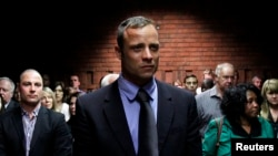 Oscar Pistorius awaits start of court proceedings while his brother looks on, Feb. 19, 2013.