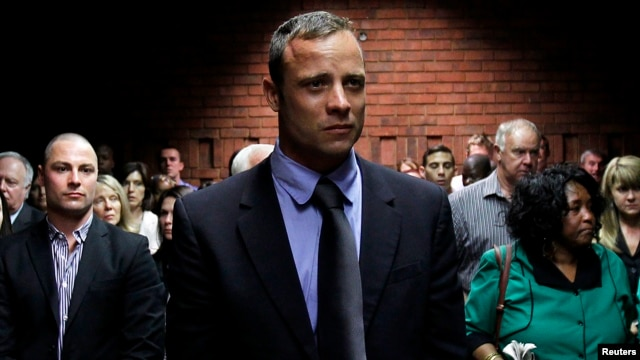 Oscar Pistorius awaits the start of court proceedings while his brother Carl (L) looks on, in the Pretoria Magistrates court February 19, 2013.
