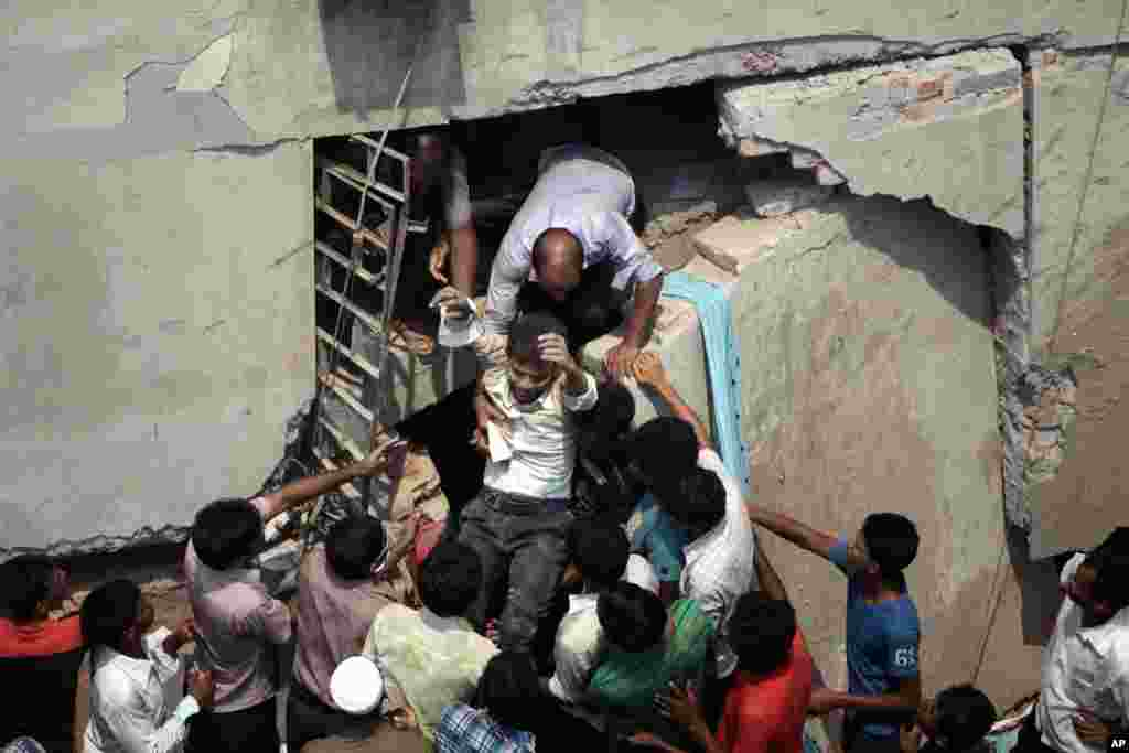 A man who was trapped in an eight-story building is rescued after the structure collapsed in Savar, near Dhaka, Bangladesh, April 24, 2013.