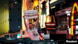 Un homme jonché sur son véhiculé brandit une pancarte qui dit que la grande majorité silencieuse soutient Donald Trump à Times Square, New York, 9 novembre 2016.