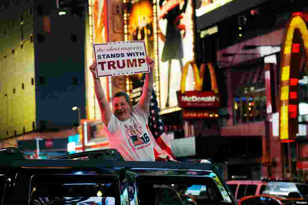 A man leans out of a Hummer shouting words in support of U.S. Republican presidential nominee Donald Trump while driving through Times Square in New York, Nov. 9, 2016.