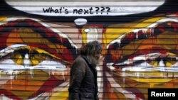 Atina'da bir duvar resminin önünden yürüyen bir Yunanlı