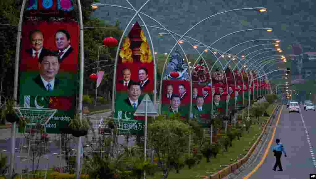 A Pakistani police officer walks past billboards showing pictures of Chinese President Xi Jinping, center, with Pakistan's President Mamnoon Hussain, left, and Prime Minister Nawaz Sharif welcoming Xi Jingping to Islamabad.