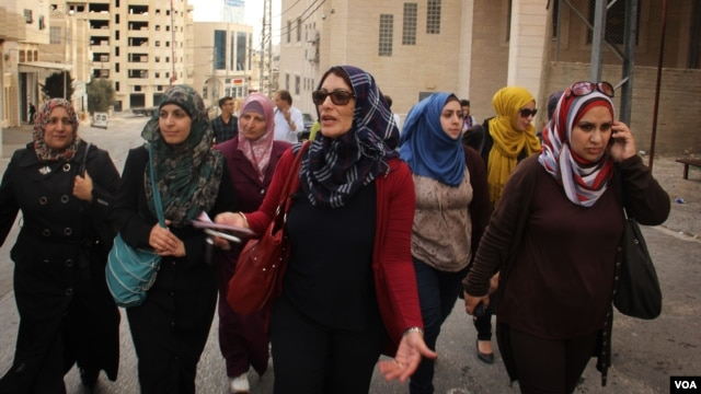 Maysoun Qawasmi and her supporters walk through a town in the West Bank ahead of the Palestinian elections. (VOA / R. Collard)