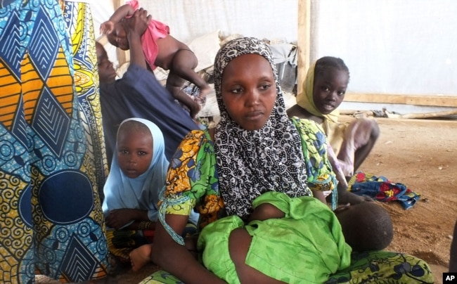 FILE - A family of refugees that fled their homes due to violence from the Islamic extremist group Boko Haram sit inside a refugee camp in Minawao, Cameroon, Feb. 25, 2015.