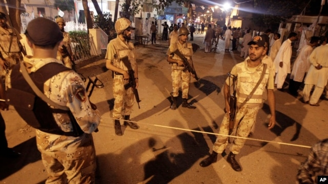Pakistani security personnel cordon off the area of blasts in Karachi, Pakistan on, May 4, 2013.