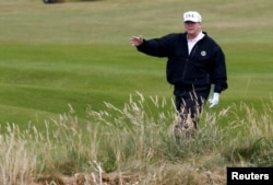 U.S. President Donald Trump gestures as he walks on the course of his golf resort, in Turnberry, Scotland, July 14, 2018.