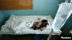 FILE - Mariam Dagane, who is infected with Rift Valley fever, rests on her bed at the Garissa hospital, 390 km (242 miles) from Nairobi, January 9, 2007.