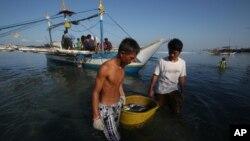 Ngư dân Philippines đưa cá đánh bắt được vào bờ. Các ngư dân nói tàu hải giám của Trung Quốc xua đuổi họ ra khỏi vùng biển tranh chấp không cho họ vào đánh bắt cá trong vùng biển từng là nơi mang lại nguồn cá phong phú từ mấy chục năm nay