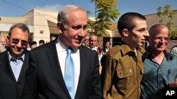 (de g. à dr.) Ehud Barak, Benjamin Netanyahu, Gilad Shalit et son père Noam (Base aérienne Tel Nof, sud d'Israël, 18 oct. 2011)