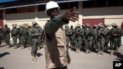 Lt. Tesnor W. Ted, 25, leader of Haiti's new national military force, points as he gathers his fellow recruits for the start of a ceremony, in the farming village of Petite Rivere de L'Aritibonite, Haiti, Sept. 16, 2013.