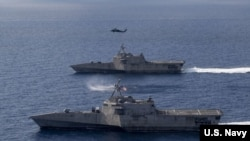 """美军""""蒙哥马利""""号(USS Montgomery)(上)和""""吉福兹""""号(USS Gabrielle Giffords)濒海战斗舰2020年1月20日在一架海鹰直升机的掩护下在南中国海执行任务。"""