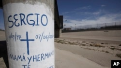 FILE - Graffiti is seen at the site where Sergio Hernandez was shot dead in 2010 under a railroad bridge connecting El Paso with Ciudad Juarez, July 1, 2014.
