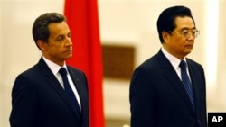 French President Nicolas Sarkozy, left, and Chinese President Hu Jintao, right, listening to the French National anthem during a welcome ceremony at the Great Hall of the People in Beijing, China, Wednesday, April, 28, 2010.