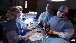 File - Dr. Keith Melancon, right, Georgetown's kidney transplant director, performs the surgery to harvest the kidney from donor Tom Otten, at Georgetown University Hospital in Washington.