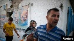 Seorang perempuan membawa barang-barangnya di sebuah sekolah yang dikelola PBB yang menampung warga Palestina, terkena gempuran tank Israel.