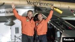 Pilot Bertrand Piccard (kanan) dan pilot cadangan Andre Broschberg,keduanya dari Swiss, melambaikan tangan mereka di depan pesawat Solar Impulse 2 (Si2), sesaat setelah mendarat di bandara internasional Tulsa, Oklahoma (12/5).