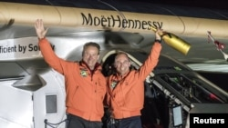 Swiss pilot Bertrand Piccard (R) and alternate pilot Andre Boschberg, also of Switzerland, wave in front of Solar Impulse 2 (Si2), the solar-powered plane, after landing at Tulsa International Airport, Oklahoma, U.S. May 12, 2016.