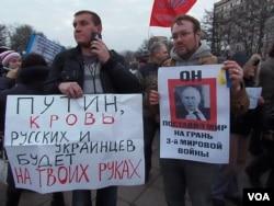 莫斯科3月7日反战集会。左侧标语: 普京,你的手上将沾染乌克兰人和俄罗斯人的鲜血。右侧标语:他让世界处在第三次世界大战边缘 (美国之音 白桦拍摄)