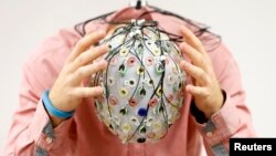 FILE - Test person Niklas Thiel poses with an electroencephalography (EEG) cap which measures brain activity, at the Technische Universitaet Muenchen (TUM) in Garching near Munich September 9, 2014. (REUTERS/Michaela Rehle)