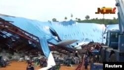 Orang-orang berdiri dekat gereja yang runtuh di tengah berlangsungnya kebaktian di kota Uyo, negara bagian Akwa Ibom, Nigeria, Sabtu, 10 Desember 2016.